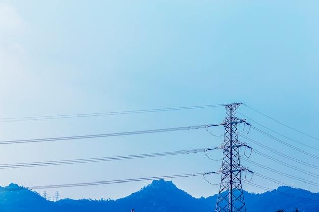 Pilão da transmissão de energia elétrica em silhueta contra o céu azul no d