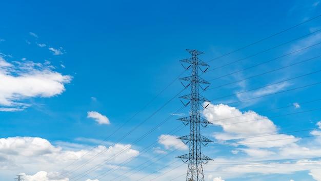 Pilão elétrico de alta tensão e fio elétrico contra o céu azul e as nuvens brancas.
