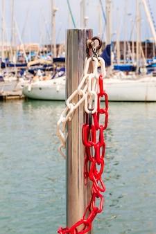 Pilar brilhante de aço com corrente de metal no fundo de iates à vela