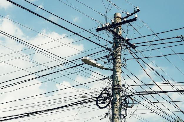 Pilar com muitos fios e uma lâmpada de rua no fundo do céu