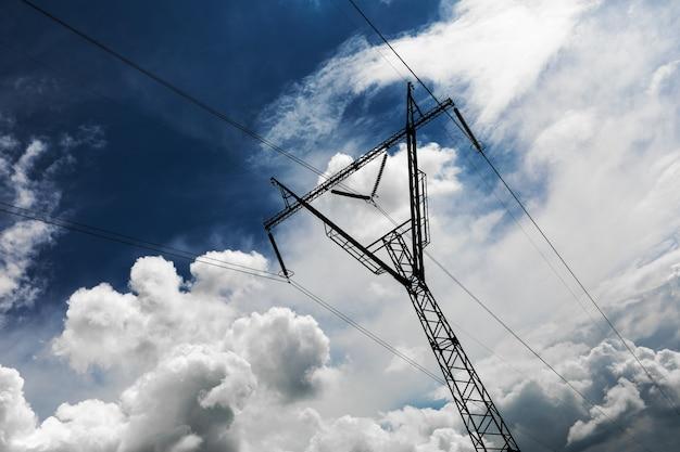 Pilar de transmissão de eletricidade em silhueta contra o céu azul