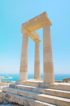 Pilar do famoso templo grego contra o céu azul claro e o mar na acrópole de lindos, no templo de rodes atena, grécia