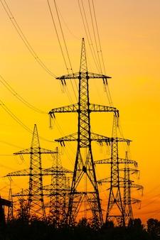 Pilares de eletricidade contra o pôr do sol laranja e amarelo