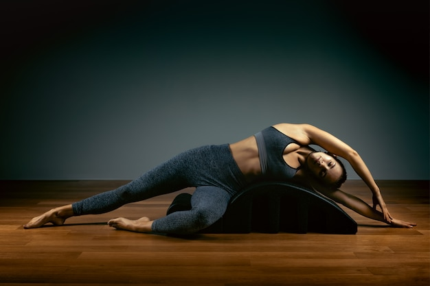 Pilates, aptidão, esporte, treinamento e conceito dos povos - mulher que faz exercícios em um tambor pequeno. conceito de fitness
