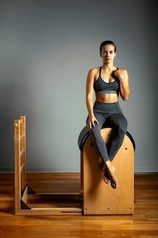 Pilates, aptidão, esporte, treinamento e conceito dos povos - mulher que faz exercícios em um tambor pequeno. correção de aparelhos impulsores, postura correta.