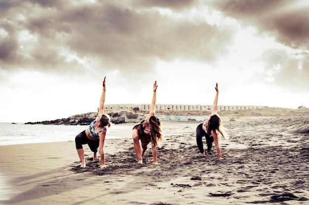 Pilates balance posicione três jovens mulheres ativas na praia fazendo atividades esportivas de fitness juntas sob um dramático céu nublado - imagem panorâmica de pessoas praticando esportes