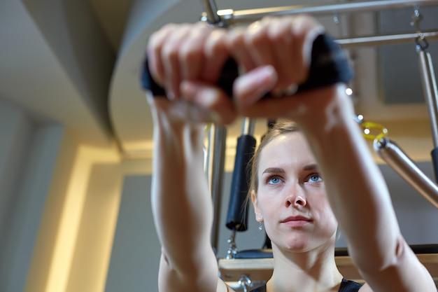 Pilates da mulher do gym que esticam o esporte na menina do instrutor da cama do reformador.