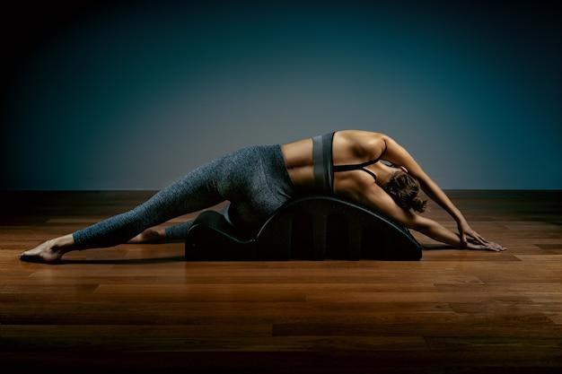 Pilates, fitness, esporte, treinamento e conceito de pessoas - mulher fazendo exercícios em um pequeno barril