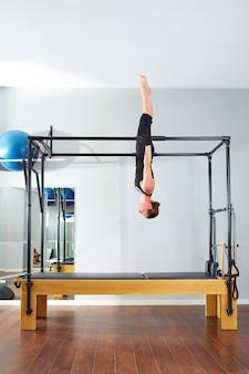 Pilates mulher em cadillac acrobático de cabeça para baixo
