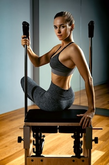 Pilates reformador cadeira mulher fitness ioga ginásio exercício. correção do sistema músculo-esquelético, belo corpo. postura correta.