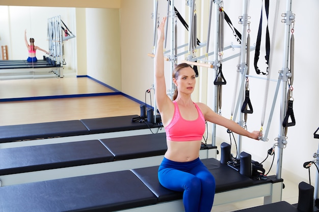 Pilates reformer lado mulher empurrar através do exercício