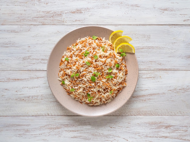 Pilau de arroz turco com orzo em um prato em uma superfície de madeira branca