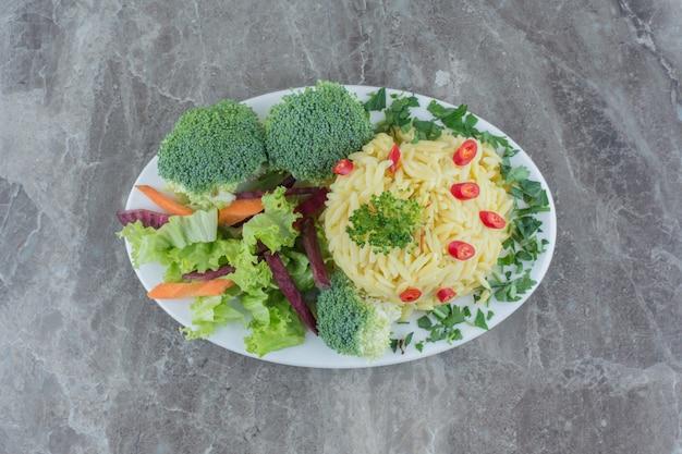 Pilau que serve guarnecido por pedaços de pimenta picada, repolho, verduras, cenoura e brócolis em uma travessa sobre mármore.