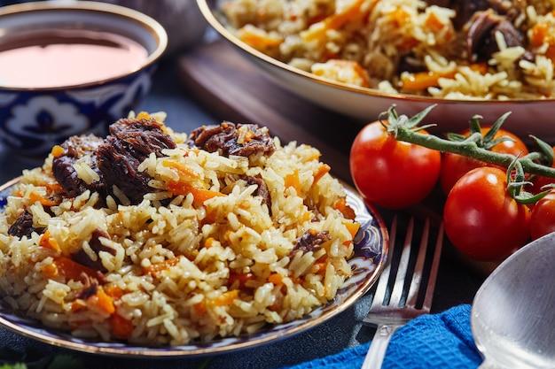 Pilau uzbeque em pratos azuis e dourados