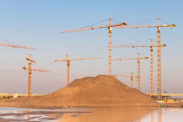 Pilha alta de areia e guindastes de torre de alta altitude do grupo no canteiro de obras, fundo do céu por do sol