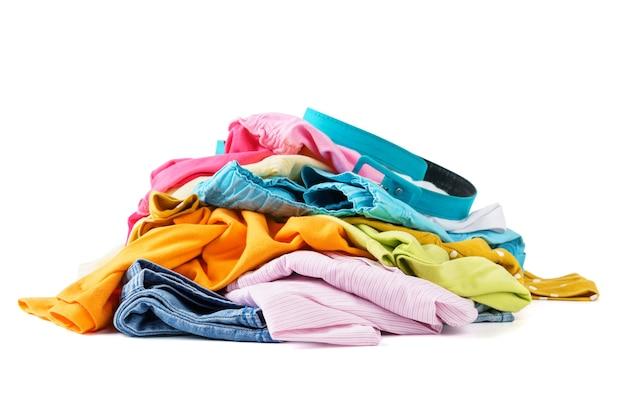 Pilha bagunçada de roupas de verão coloridas isoladas em branco.