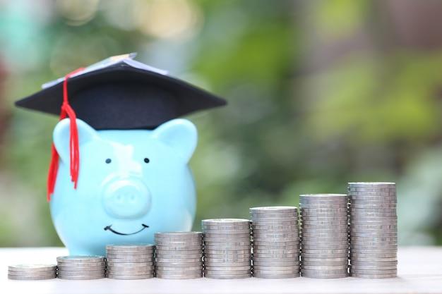 Pilha crescente de dinheiro de moedas com chapéu de formatura no porquinho