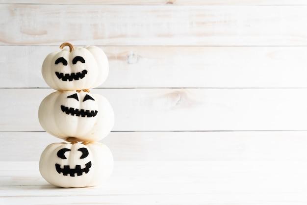 Pilha da abóbora branca do fantasma no fundo de madeira branco. conceito de halloween