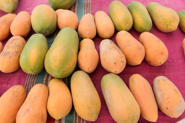 Pilha da papaia amarela madura para a venda no mercado.