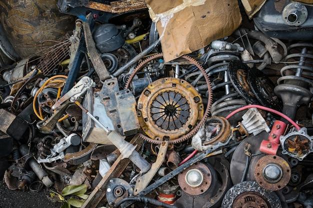 Pilha das peças dos carros velhos abandonados em um montão dos desperdícios.