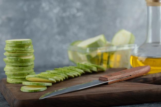 Pilha de abobrinhas fatiadas na placa de madeira com faca e garrafa de óleo.