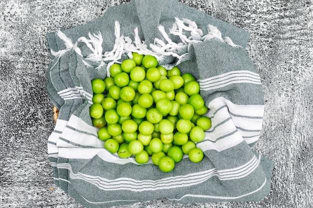 Pilha de ameixas verdes vista superior na toalha de cozinha e grunge
