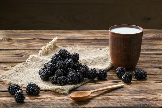 Pilha de amora fresca no guardanapo de pano de saco e copo de barro com leite na mesa de madeira
