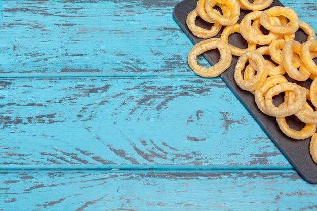 Pilha de anéis de cebola crocante em fundo de madeira