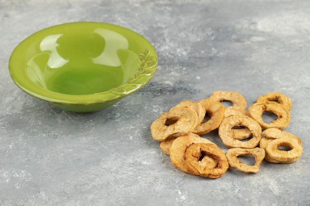 Pilha de anéis de maçã seca orgânica e tigela vazia no mármore.