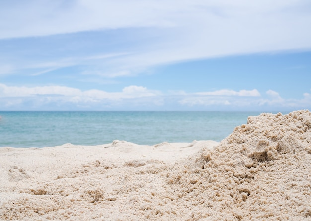 Pilha de areia da praia em desfocar a imagem do mar azul e o céu azul.