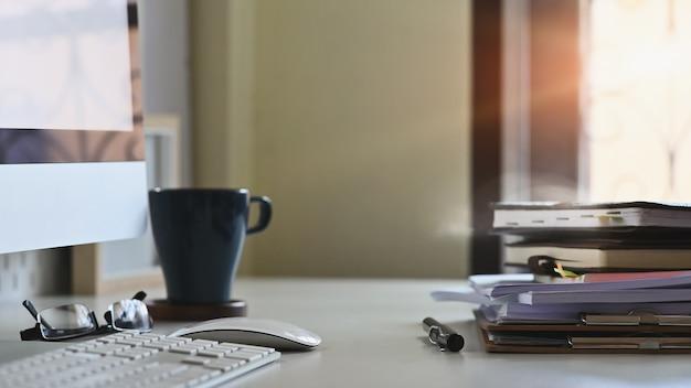Pilha de arquivos em papel e equipamentos de negócios de caneta na mesa de escritório.