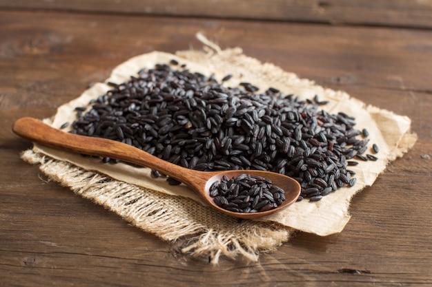 Pilha de arroz preto com uma colher em uma mesa de madeira