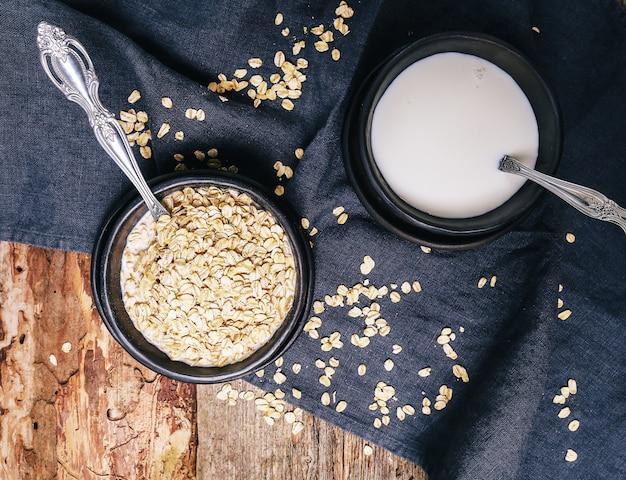 Pilha de aveia em uma tigela e copo de leite