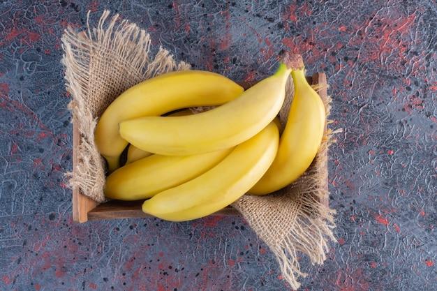 Pilha de banana em caixa de madeira em superfície colorida