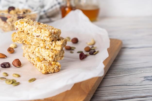 Pilha de barras de granola caseiras saudáveis com nozes, mel e frutas secas na mesa de madeira