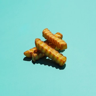 Pilha de batatas fritas no fundo colorido