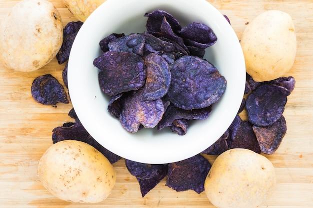 Pilha de batatas fritas roxas no fundo de madeira