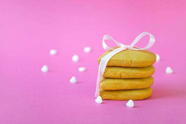 Pilha de biscoitos amanteigados amarrados com fita rosa e muitos confetes doces em formato de coração branco