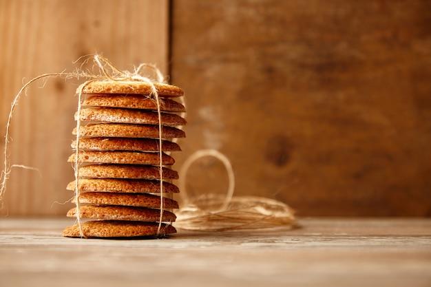 Pilha de biscoitos amarrados com corda artesanal na mesa de madeira. ideia do presente de feriado.