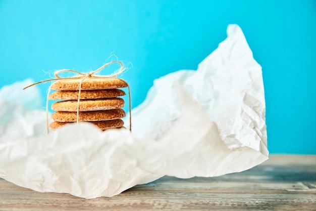 Pilha de biscoitos amarrados com corda em papel branco desfocado