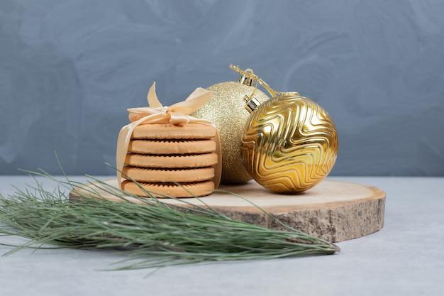Pilha de biscoitos amarrados com fita e bolas de natal na placa de madeira. foto de alta qualidade