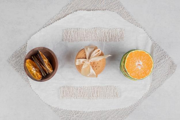 Pilha de biscoitos amarrados com laço e fatias de tangerina no fundo de mármore. foto de alta qualidade