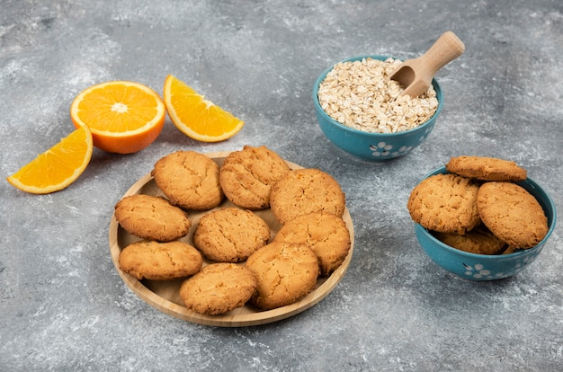 Pilha de biscoitos caseiros e aveia com laranja sobre mesa cinza.