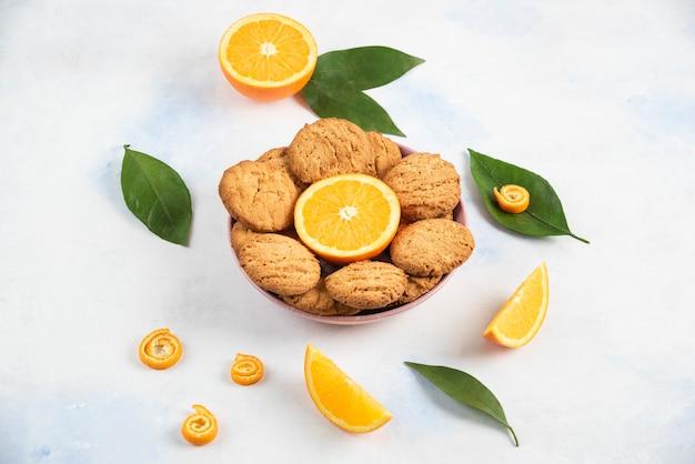 Pilha de biscoitos caseiros frescos com fatias de laranja.