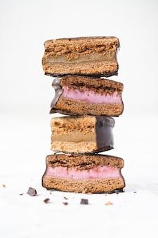 Pilha de biscoitos com cobertura de chocolate com recheio de morango.