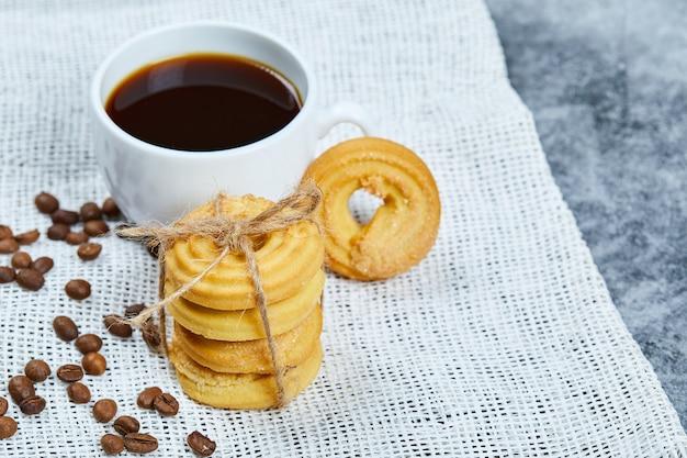 Pilha de biscoitos com grãos de café e uma xícara de café em uma toalha de mesa branca.