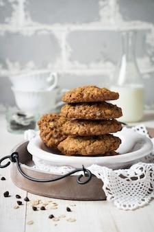 Pilha de biscoitos de aveia com chocolate em uma luz com flocos e uma garrafa de leite.