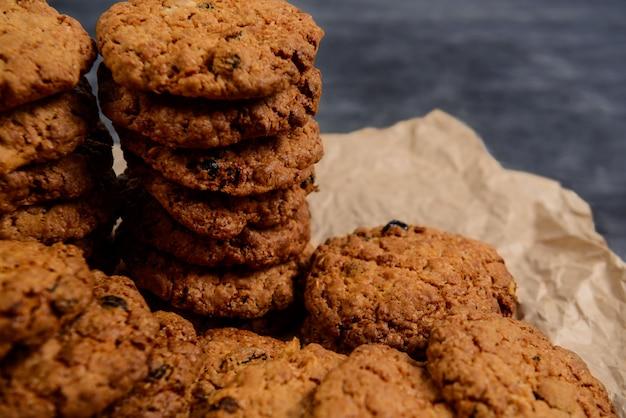Pilha de biscoitos de aveia doce no papel manteiga na mesa de madeira