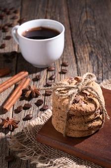 Pilha de biscoitos de chocolate, uma xícara de café na velha mesa de madeira