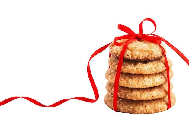 Pilha de biscoitos de gengibre de natal amarrados com fita vermelha isolada no branco